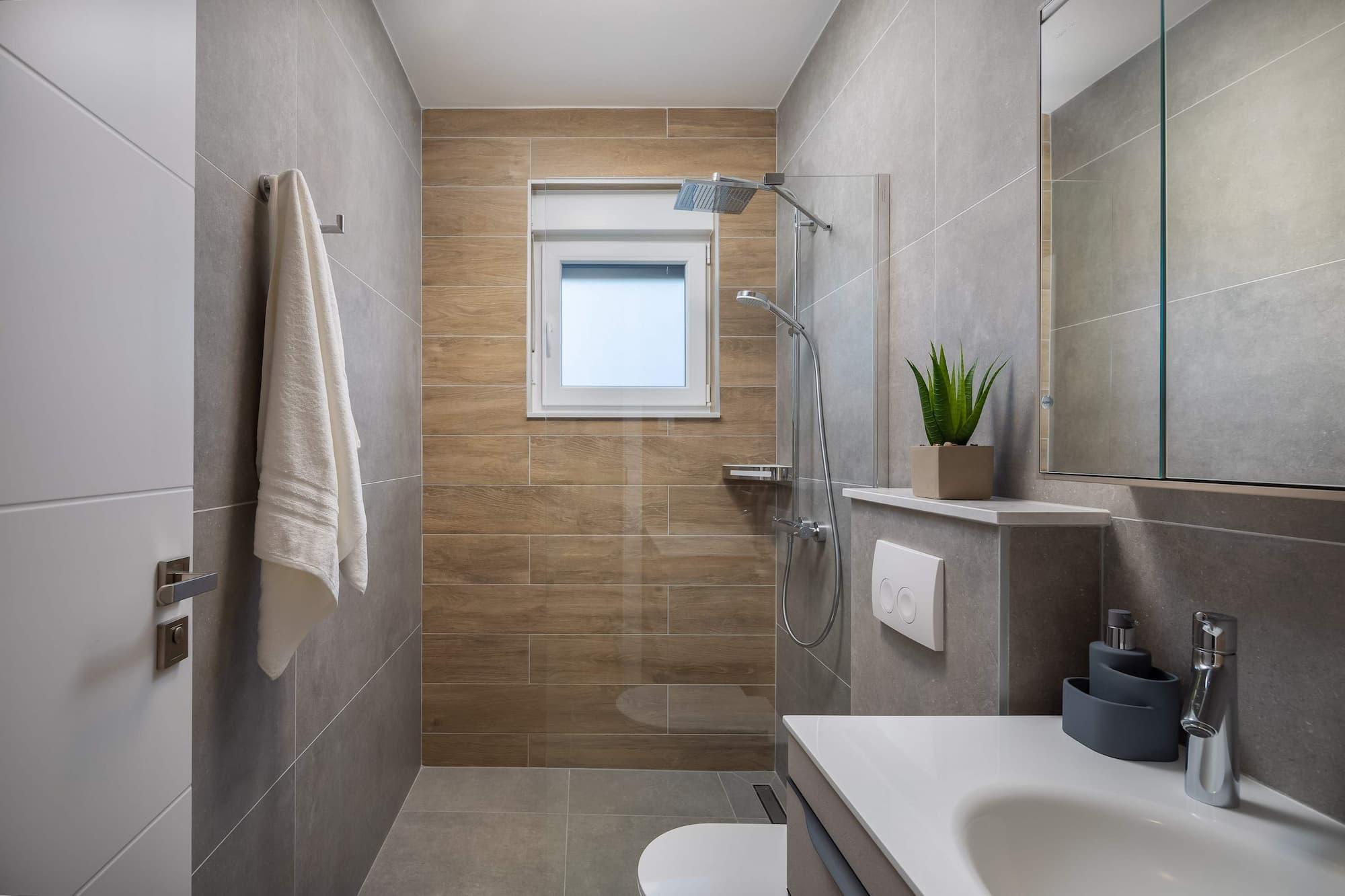 Vila za odmor s bazenom u Hrvatskoj, kupaonica sa sivim pločicama, umivaonikom i tušom