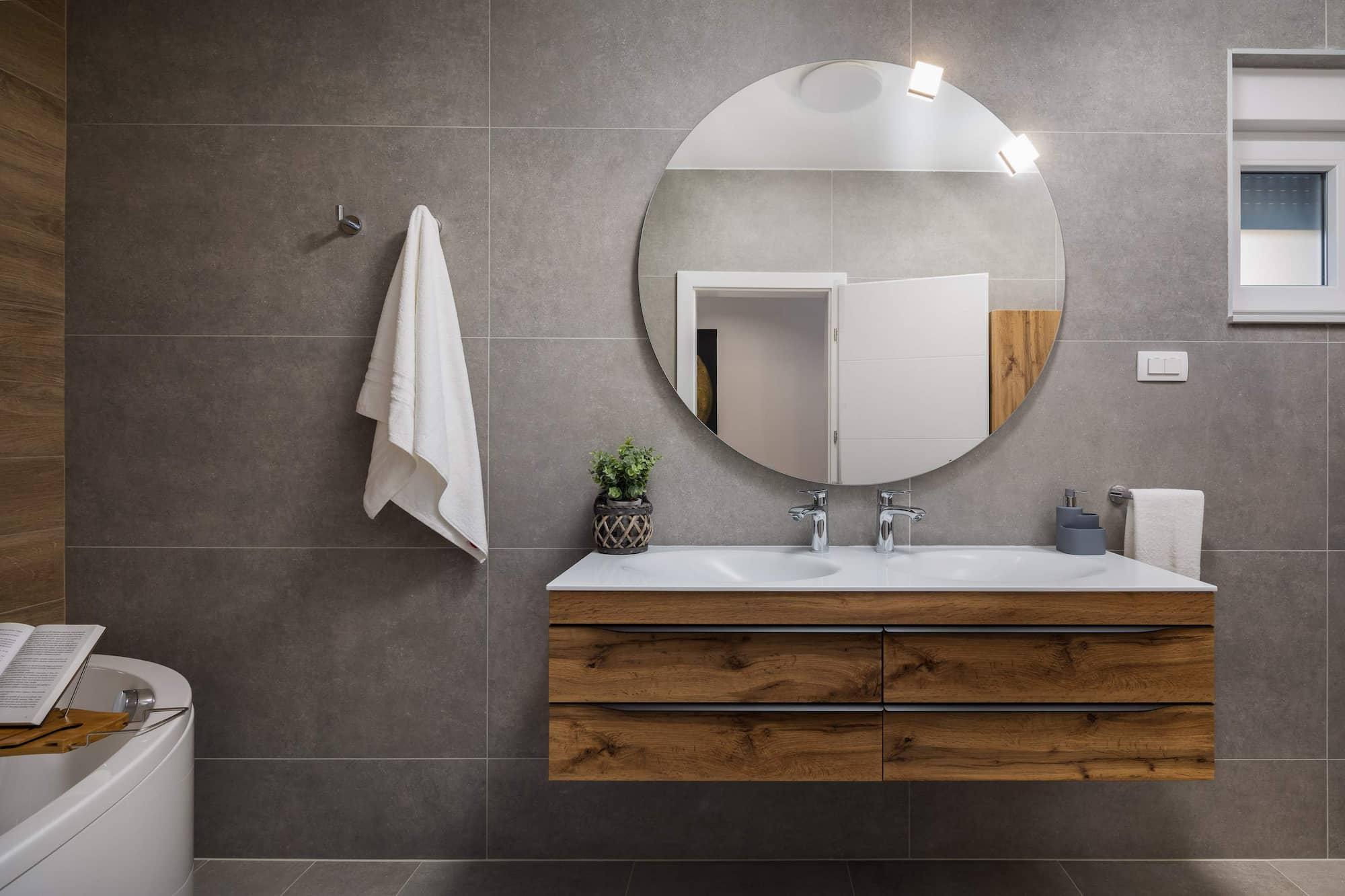 Vila za odmor s bazenom u Hrvatskoj, kupaonica sa sivim pločicama i dva umivaonika te velikim okruglim ogledalom