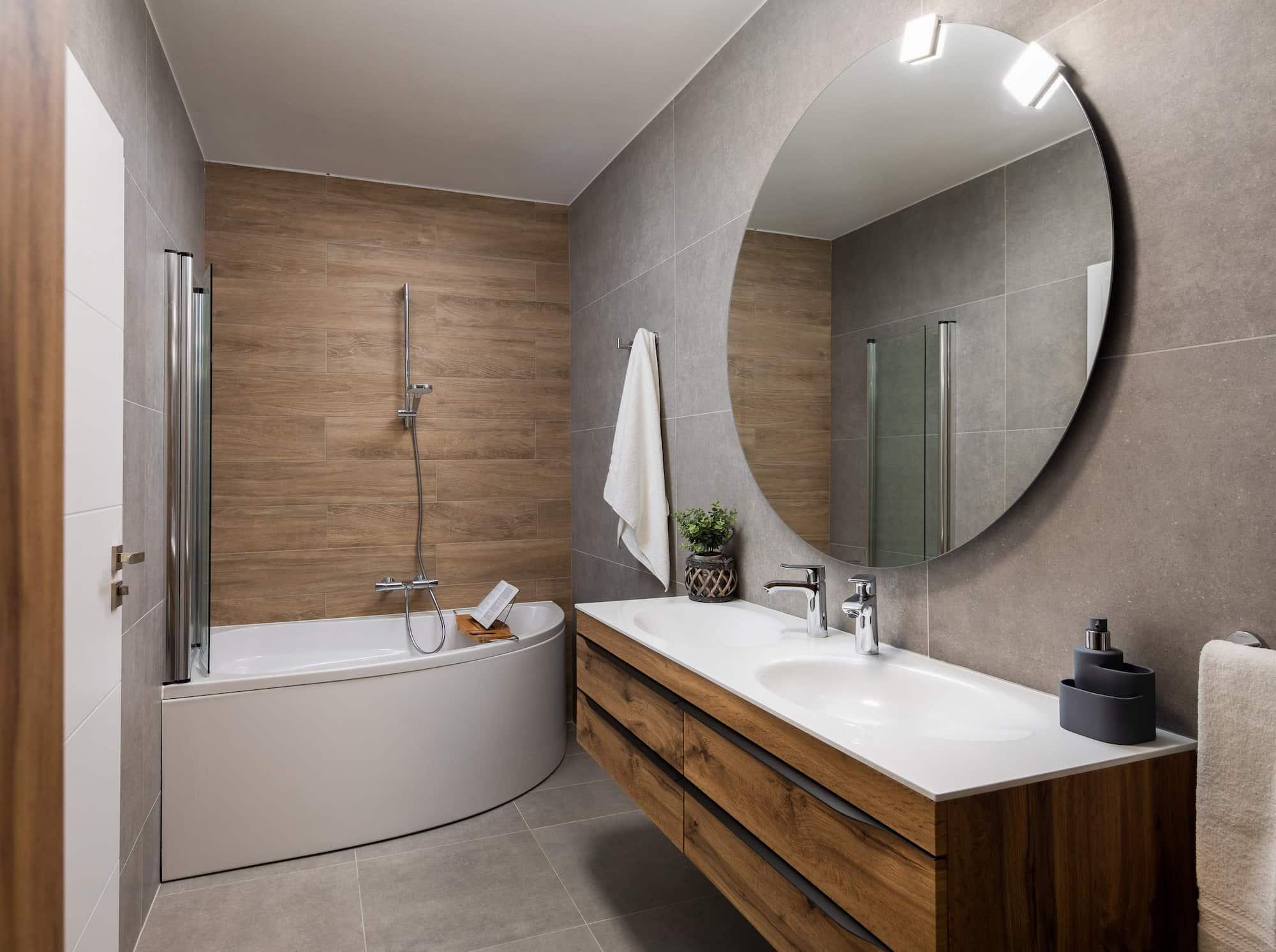 Vila za odmor s bazenom u Hrvatskoj, kupaonica sa sivim i drvenim pločicama te s dva umivaonika i velikom kadom