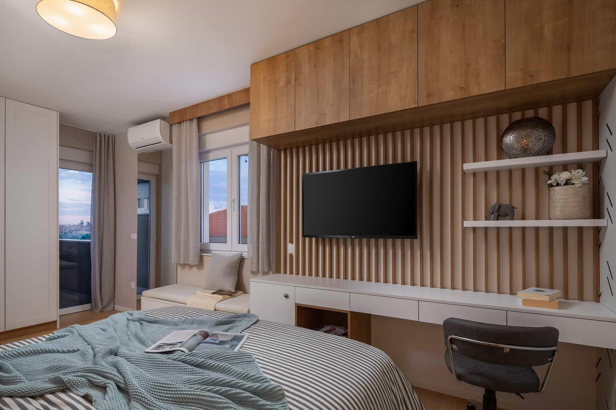 Vila za odmor s bazenom u Hrvatskoj, televizija i radni stol s drvenim detaljima u spavaćoj sobi